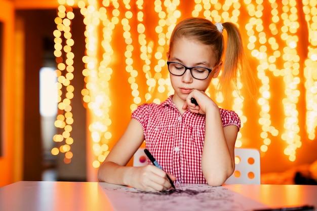 サンタクロースを描く大きな黒い眼鏡のブロンドの女の子。クリスマスと新年のテーマ、黄色のボケ Premium写真