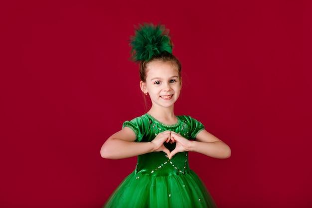 赤い壁に分離された豪華な緑のドレスで踊る美しい少女プリンセス。衣装のカーニバルパーティー Premium写真