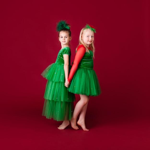 赤い壁に分離された豪華な緑のドレスで踊る美しい少女王女。衣装のカーニバルパーティー Premium写真
