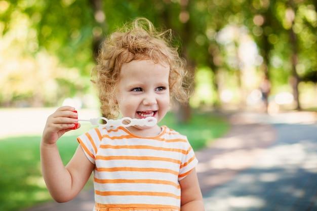 プリンセスガールのハート型、幸せな子供時代のコンセプトでシャボン玉を吹く Premium写真