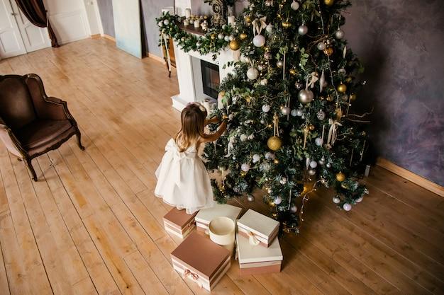 Милая маленькая девочка в белом платье с большими подарками возле елки Premium Фотографии