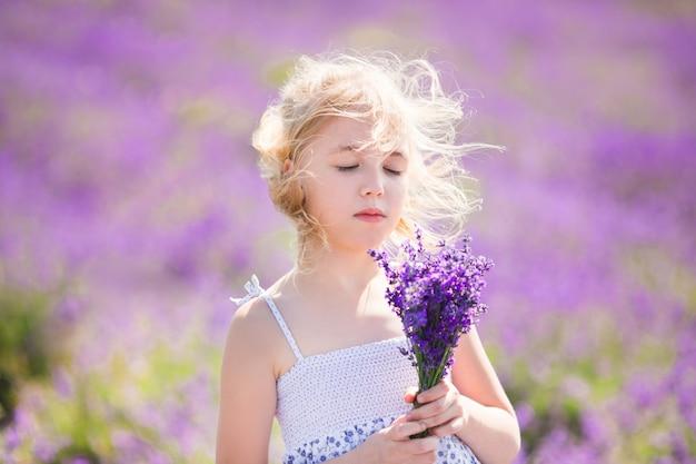 彼女の手に小さなブーケとラベンダー畑の色のドレスのブロンドの女の子 Premium写真