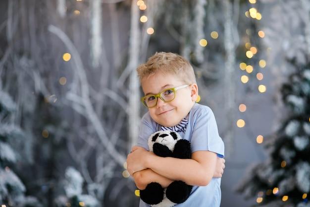 Портрет рождества счастливого мальчика ребенка с большими стеклами держа игрушку носит крытую студию Premium Фотографии