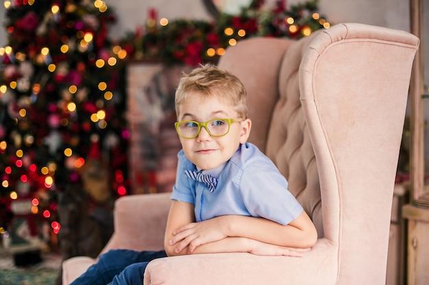 Очаровательный маленький белокурый мальчик в синей рубашке с большими очками сидит на кресле Premium Фотографии