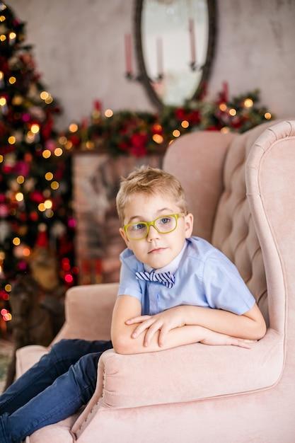 Маленький белокурый мальчик в синей рубашке с большими очками сидит на кресле Premium Фотографии