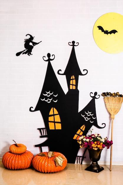 Черный сказочный замок, ведьма на белой стене и декоративные тыквы. декор для празднования хэллоуина Premium Фотографии