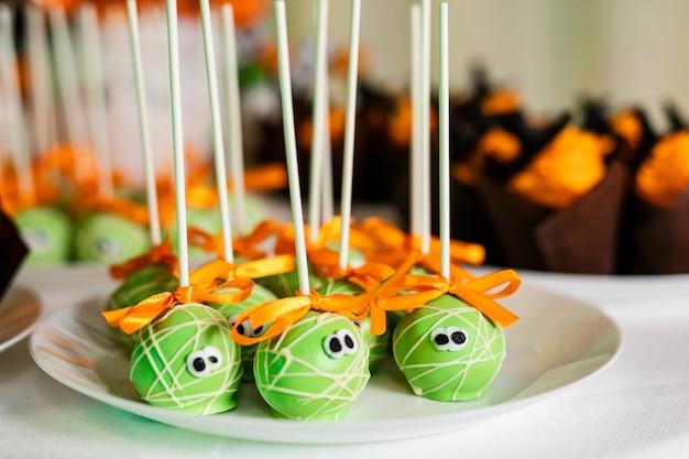 ハロウィーンのお祝いのためのキャンディーバーの上の緑のポップケーキ Premium写真