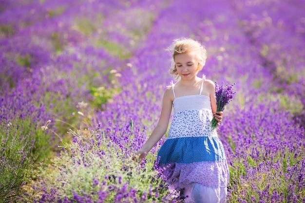 花の小さなブーケとラベンダー畑の青いドレスのブロンドの女の子 Premium写真