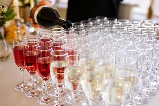 ウェイターは、路上で結婚式のケータリングでグラスにシャンパンを注ぐ Premium写真