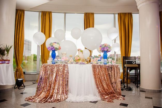 さまざまなキャンディー、カップケーキ、スフレ、ケーキがたくさんあるゴールデンウェディングパーティーのキャンディーバー。 Premium写真