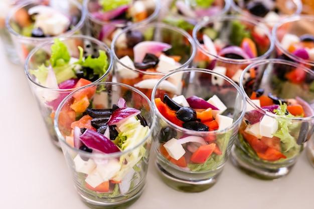 新鮮なサラダ、卵、サーモン、キュウリの白いテーブルの上に立っている小さなグラス Premium写真