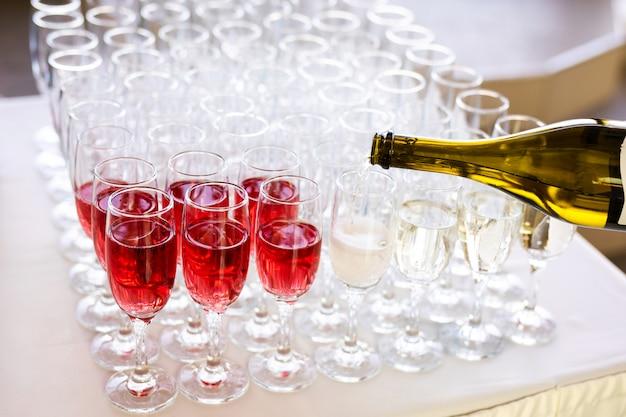 ウェイターは路上でグラスにシャンパンを注ぐ-結婚式のケータリング Premium写真