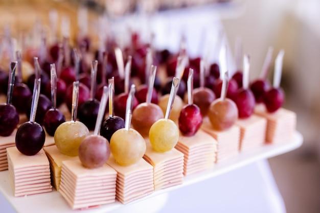 ビュッフェテーブルのプレートで軽食。各種ミニカナッペ、珍味とスナック、イベントでのレストランの食事。赤ぶどう、チーズ、ハム Premium写真