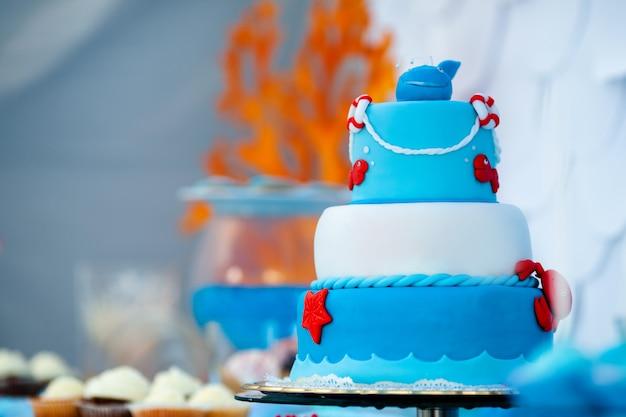 甘いカニ、魚、ヒトデ、面白いクジラの上の青と白の巨大なバースデーケーキ Premium写真