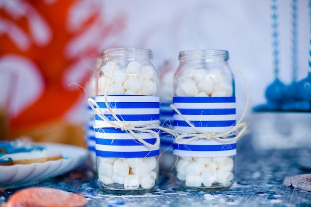 海の装飾とお菓子、キャンディー、クッキーのプレート、マシュマロの瓶を飾るテーブル Premium写真