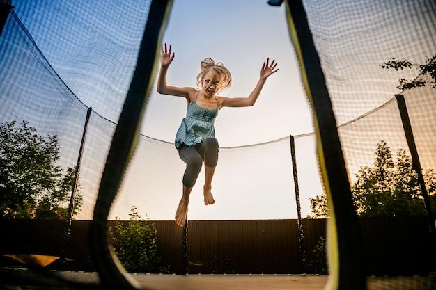 Девочка прыгает высоко на большой батут на улице в саду на закате лета Premium Фотографии