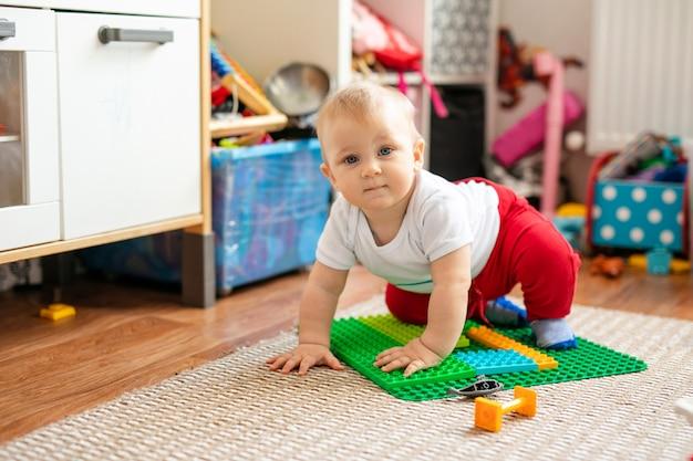 Маленький мальчик в белой футболке с игрушками на полу у себя дома Premium Фотографии