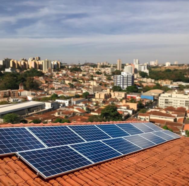 晴れた日に住宅の屋根の上の太陽光発電 - 持続可能な資源の太陽エネルギーの概念 Premium写真