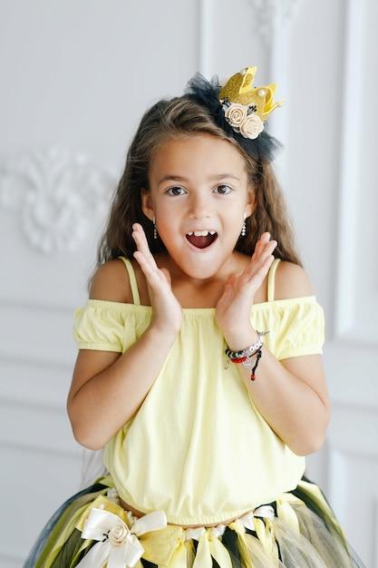 手作りの王冠とブレスレットで美しく服を着て面白い女の子モデル Premium写真
