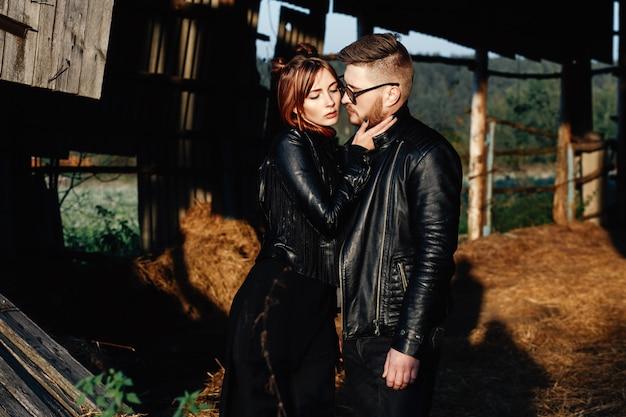 彼のガールフレンドとファッション男は黒い革のジャケットに立って、お互いを見て Premium写真