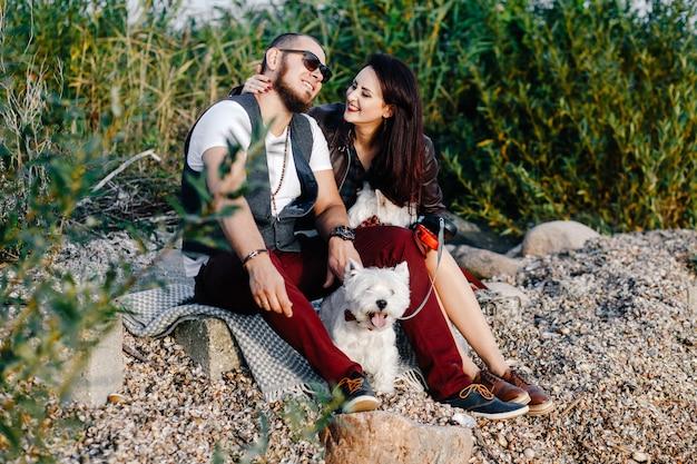 白い犬と一緒に海岸に座っているスタイリッシュな愛情のあるカップル Premium写真