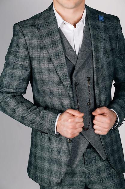 グレーの市松模様のスーツのスタイリッシュな男 Premium写真