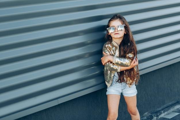 灰色の壁に対してトレンディな女児の肖像画 Premium写真