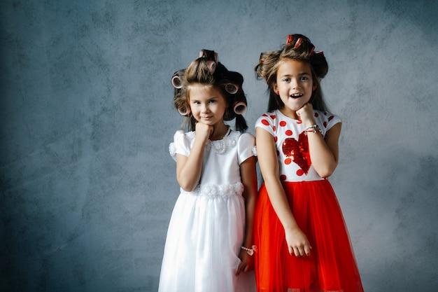 壁にポーズのヘアカーラーとドレスの面白い女の子 Premium写真