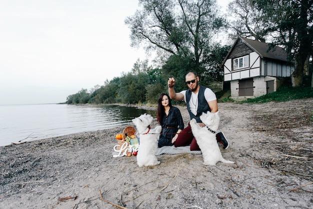 白い犬と遊ぶビーチで愛するカップル Premium写真