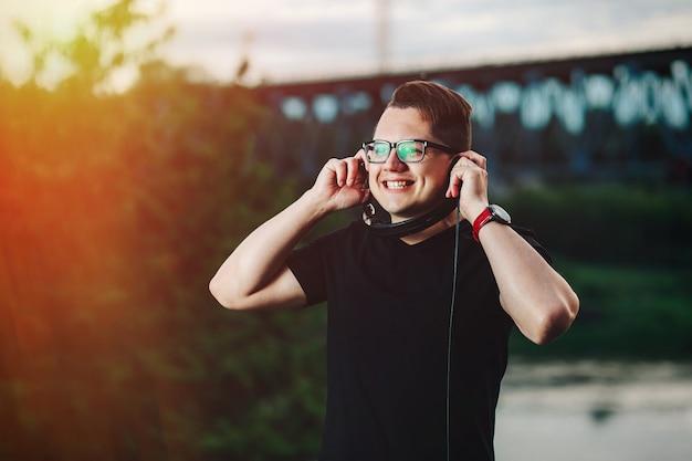 日光の下で音楽を聞いて幸せなハンサムな男 Premium写真
