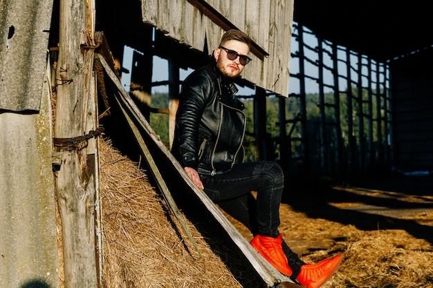 革のジャケットと赤いスニーカーのひげを生やした男は、放棄された建物の背景に座っています。 Premium写真