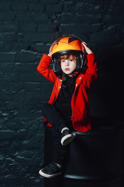 Мальчик в шлеме под люстрой в тускло освещенной комнате Premium Фотографии