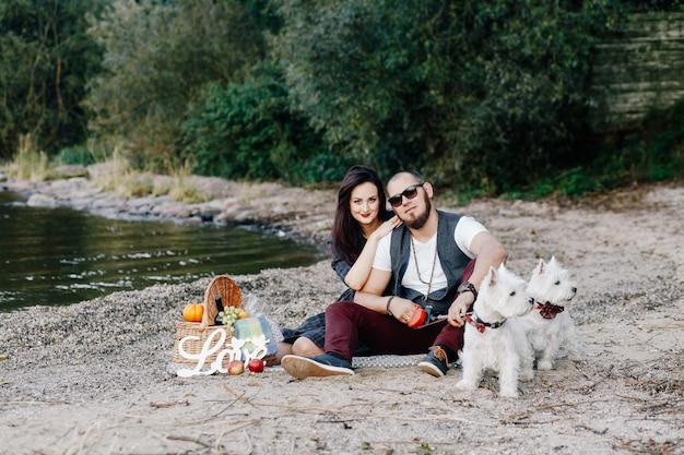公園で彼らの白い犬を歩いて美しい妻と夫 Premium写真