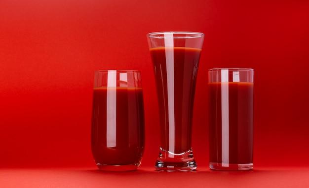 Стакан томатного сока, изолированных на красный Premium Фотографии