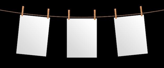 黒の背景に分離されたロープにぶら下がっている空の紙シート、プロジェクト、ポスターテンプレートのモックアップ Premium写真
