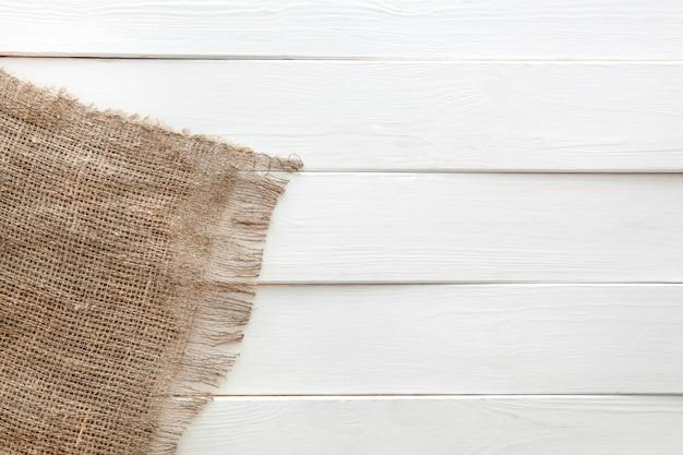 白い木製の背景に黄麻布 Premium写真