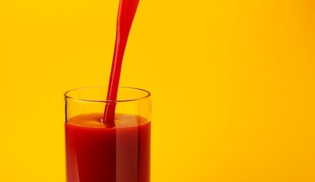 Томатный сок наливание в стакан, изолированные на желтый Premium Фотографии