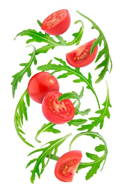 落ちてくる新鮮な野菜。チェリートマトと白で隔離されるルッコラ Premium写真