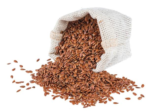 黄麻布の袋の白い背景で隔離の亜麻の種子 Premium写真