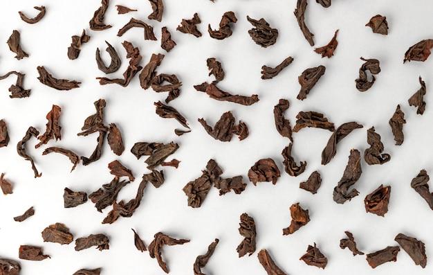 Сухие листья черного чая, изолированные на белом, вид сверху Premium Фотографии