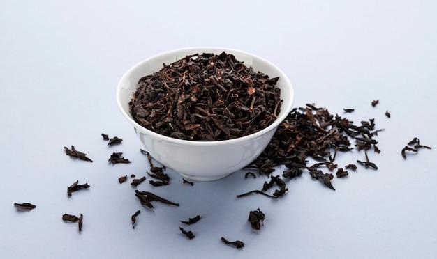 Сухие листья черного чая, изолированные на белом Premium Фотографии