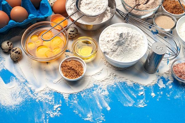 Выпечка ингредиенты на синем фоне Premium Фотографии