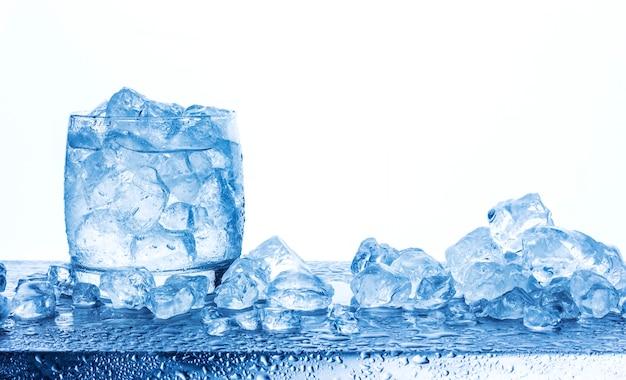 白い背景で隔離のガラスの砕いた氷で水します。 Premium写真