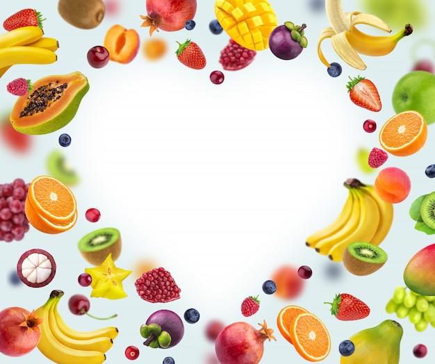 白で隔離され、さまざまな果物や果実から成っているハート形フレーム Premium写真