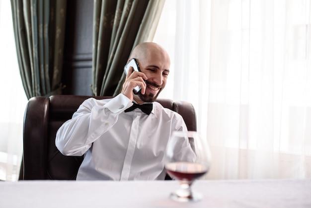 レストランで電話で話している男性。 Premium写真