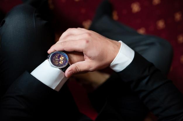 Мужчина смотрит на часы Premium Фотографии