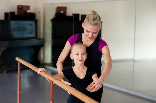 振付師は子供にバレエの位置を教えます Premium写真