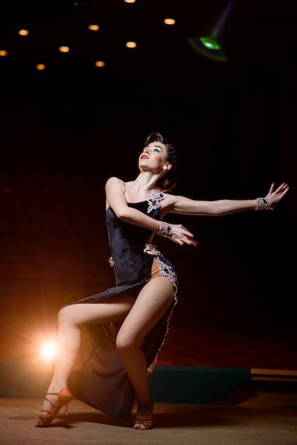 ステージで踊る黒のドレスで美しい少女。 Premium写真