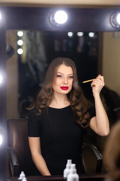 Красивая девушка делает макияж и смотрит в зеркало Premium Фотографии