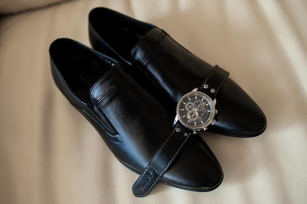 Черные мужские туфли и часы Premium Фотографии